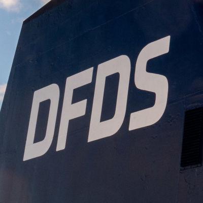 En skorsten på ett stort fartyg där det står DFDS.