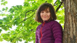 En ung flicka uppflugen i ett träd. Hon tittar in i kameran och ler.