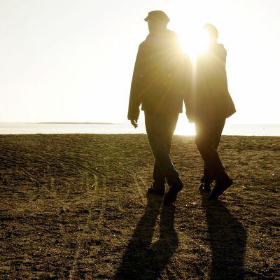 Iäkäs pariskunta ulkoilemassa meren rannalla.