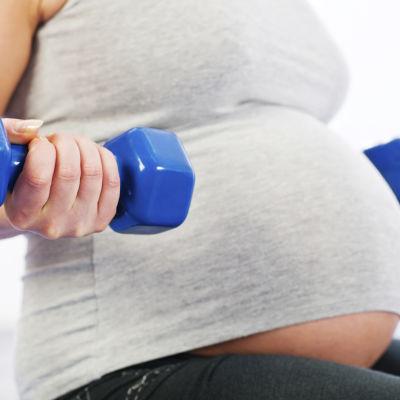 Gravid kvinna tränar.