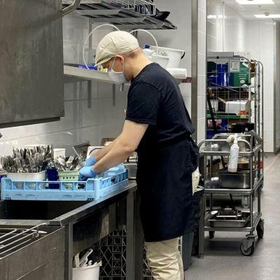 Jyri Lähteenmäki järjestelee tiskikoneeseen meneviä astioita ravintolan tiskihuoneessa.
