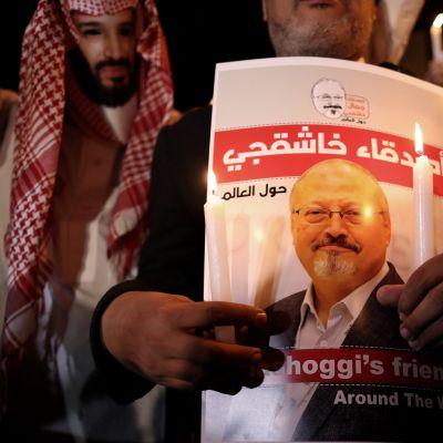Mielenosoittaja piti Jamal Khashoggin kuvaa Istanbulissa lokakuussa 2018. Vasemmalla puolella toinen mielenosoittaja oli pukeutunut Saudi-Arabian kruununprinssiä esittävään naamariin.