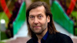 Jan-Erik Andersson står framför hjärtformad bro och ser in i kameran