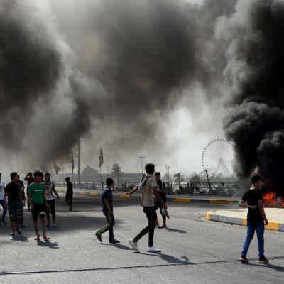 Mielenosoittajat polttavat autonrenkaita Irakin pääkaupungissa Bagdadissa keskiviikkona.