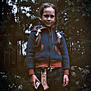 Lettipäinen alle kymmenvuotias tyttö seisoo puukko vyöllään ja tulitikkuaski vasemmassa kädessä metsässä.