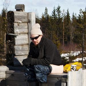 Pipopäinen mies istuu seinättömässä huussissa kevättalvella.