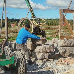 Kaksi miestä rakentamassa kirkkoa työkoneen avustamana.