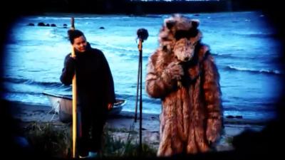 En fiskare och en person klädd i björnkostym står på en sandstrand. En liten roddbåt är uppdragen i strandvattnet.