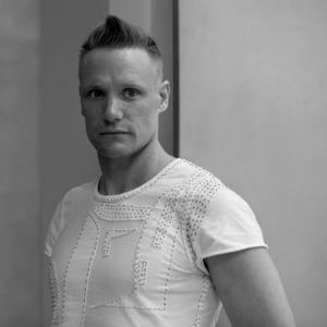 Timo Rissanen, professor i mode och hållbarhet vid Parsons New School of Design i New York. Ung kortklippt man i vit t-skjorta.