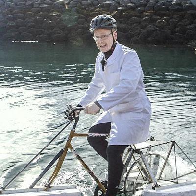 Ævar försöker cykla på vattnet iförd en vit rock.