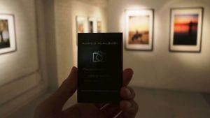 En hand som håller ett svart visitkort, i bakgrunden fotografier på en vit vägg.