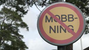 En skylt som förbjuder mobbning. Ser ut som en förbudsskylt i trafiken.