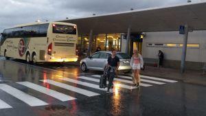 En buss står utanför Vasa flygplats. Två personer med resväskor går över vägen. Det är blött på marken.