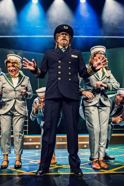 Dansgrupp i sjömanskläder och kaptenen i mitten.