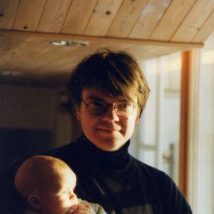 Silmälasipäinen, hymyilevä mies pitelee sylissään vauvaa.