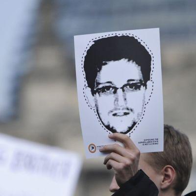 hand håller uppe Edward Snowden-bild som mask att klippa ut.