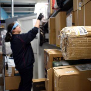 En person plockar upp paket i hyllan i en mataffär.