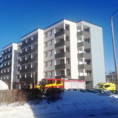 Brandbil och en ambulans på en parkering till ett höghus.