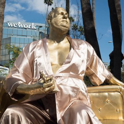 Kylpytakkiin pukeutunut elokuvatuottaja Harvey Weinstein istuu sohvalla Oscar-patsas kädessään.