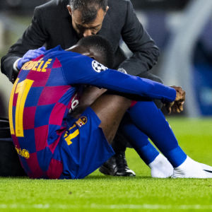 Ousmane Dembele rådfrågas av medicinsk personal då han sitter nedhukad.