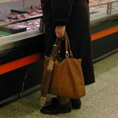 Person som håller väska och paraply vid en köttdisk.