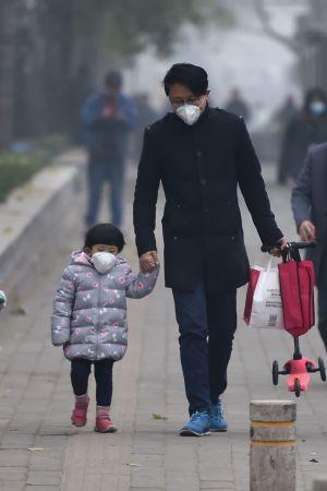 En kinesisk pappa och dotter har på sig ansiktsmasker när de promenerar i luftförorenade Peking.