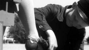 Poika kiillottaa naisen kenkiä