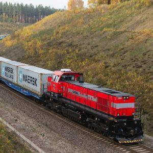 Ett rött lokomotiv med gråa vagna med Maersks logotyp.