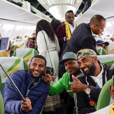 Matkustajat ottavat selfieitä lentokoneessa.