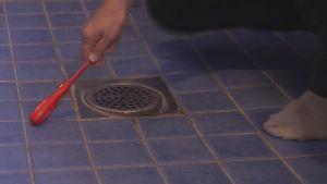 Kuntotarkastuksessa tutkitaan lattialaattojen kiinnityksen lujuutta.