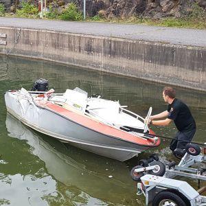 En aluminiumbåt har varit med om en olycka till havs, där en större båt kört in i styrbordssida på båten. Den dras upp på en trailer efter olyckan.