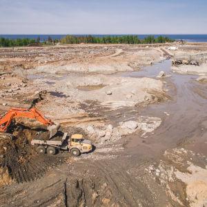 Fennovoimas byggarbetsplats i Pyhäjoki. En orange grävskopa fyller jord i en gul lastbil på ett stort hyttjigt fält.
