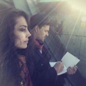 Nainen ja mies istuvat ilta-auringossa katolla. Sivukuvassa etualalla nainen, jolla on pitkät, kiharat hiukset. Hänen takanaan hattupäinen mies piirtää lehtiöön.