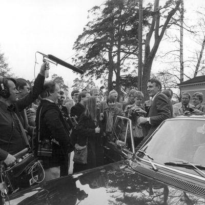 Mauno Koivisto nousee autosta, ja on toimittajien ympäröimänä.