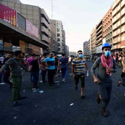 Mielenosoittajia perääntymässä sen jälkeen, kun turvallisuusjoukot ampuivat kyynelkaasua kohti mielenosoitusta.