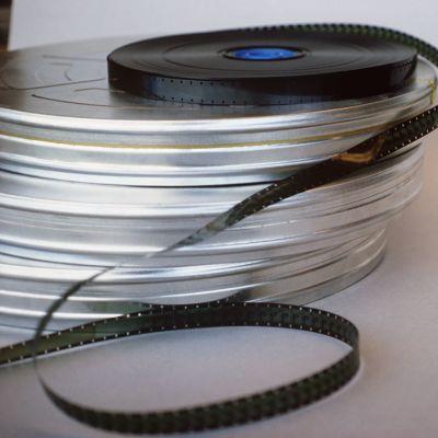 Pino vanhoja elokuvafilmirullia, päällimmäisenä avattu filmirulla.