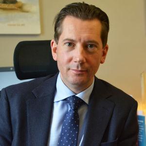 En man i kostym sitter på en skrivbordsstol. Bakom honom syns tavlor och vimplar.