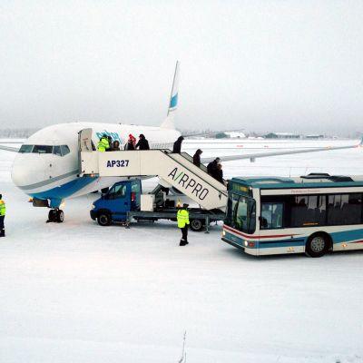 Ensimmäinen Rovaniemelle laskeutunut charterkone tyuli Varsovasta. Matkustajat siirtyvät koneesta linja-autoon.