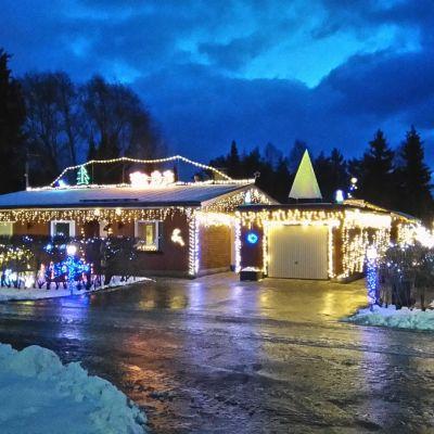 Talo käärittynä jouluvaloihin