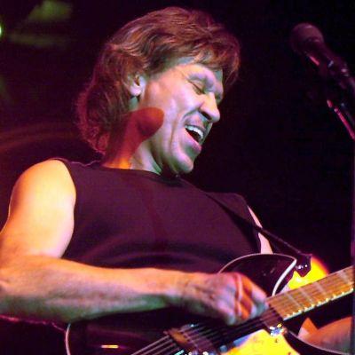 John Kay från Steppenwolf spelar elgitarr och ler brett med öppen mun.