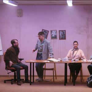 Fem skådespelare sitter bakom ett långt mötesbord i ett sjabbigt kontor.