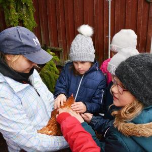 Flera barn står i ring kring en kvinna som håller i en höna.