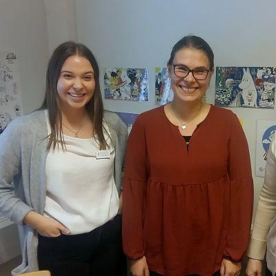 Tre kvinnor poserar vid en vägg.