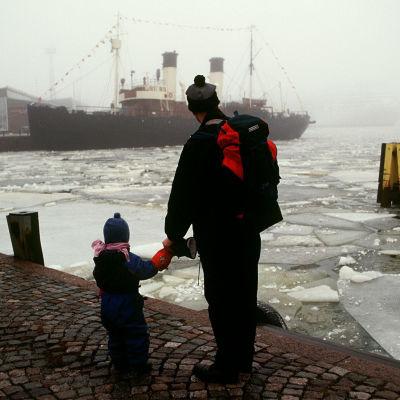 En man och en pojke står i hamnen i Helsingfors och ser ut över vattnet på en ångbåt