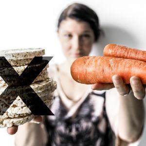 Nainen pitää käsissään porkkanoita ja riisikakkuja