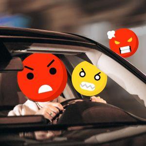 Auto, kuljettajan kasvojen paikalla kiukkuisia hymiöitä.