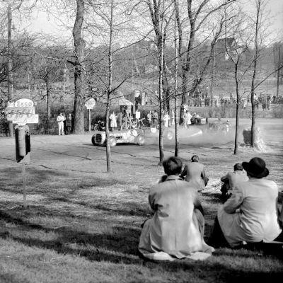 Eläintarhan ajot äitienpäivänä 1951. Autojen kilpa-ajot, yleisöä radan varrella katselemassa autojen kilpa-ajoa.