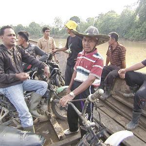 Palmuöljytilalla työskenteleviä miehiä veneessä