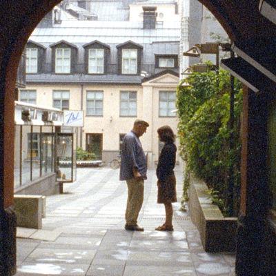 vanhempi mies ja nuori nainen seisovat vastakkain pihalla