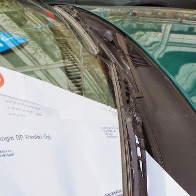 OP:n laskuja kuoressa auton tuulilasinpyyhkijässä.